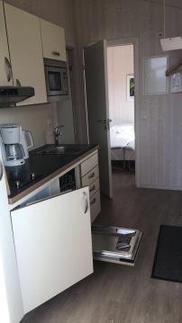 Eine kleine Küche, hinten das Schlafzimmer